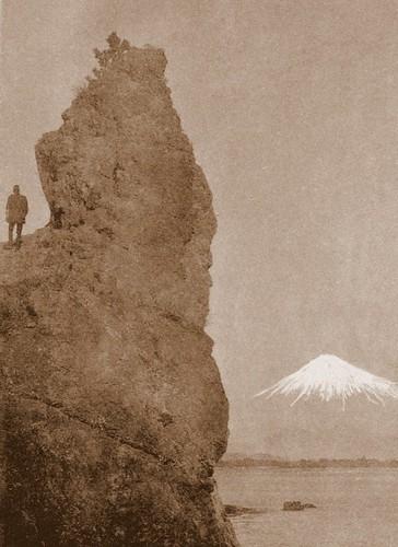 MAN AND ROCK LOOKING AT SNOW-CAPPED MT. FUJI