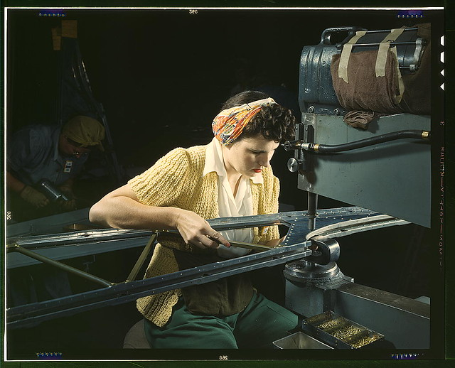 "A girl riveting machine operator at the Douglas Aircraft Company plant joins sections of wing ribs to reinforce the inner wing assemblies of B-17F heavy bombers, Long Beach, Calif. Better known as the ""Flying Fortress,"" the B-17F bomber is a later model o"