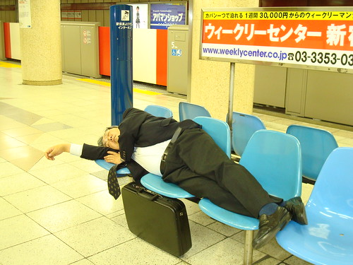 Photo of a Tokyo businessman asleep in a subway station