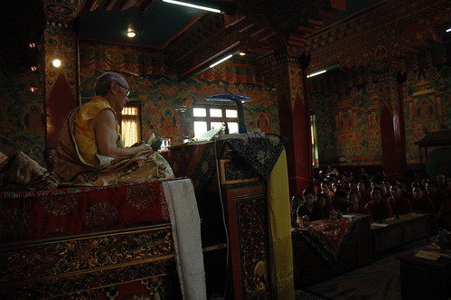 His Holiness Jigdal Dagchen Sakya, on his throne, wearing traditional style silk garments, white and yellow katag, Tharlam Monastery, Boudha, Kathmandu, Nepal with monks and sangha, traditional wall murals of Lord Buddha's lifestory by Wonderlane