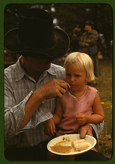 Homesteader feeding his daughter at the Pie Town, New Mexico Fair free barbeque  (LOC) (The Library of Congress) Tags: food newmexico girl hat cake pie cowboy child eating father daughter blond blonde libraryofcongress barbeque pietown fatherdaughter youngchild catroncounty homesteader russelllee xmlns:dc=httppurlorgdcelements11 dc:identifier=httphdllocgovlocpnpfsac1a34142 oct1940