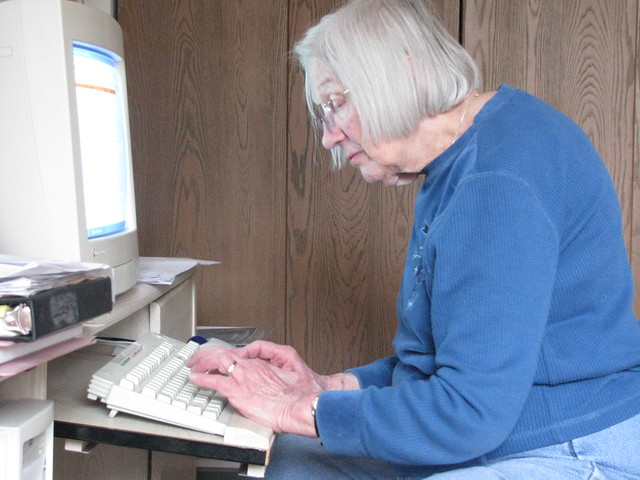 Photograph of a senior citizen working at a desktop computer