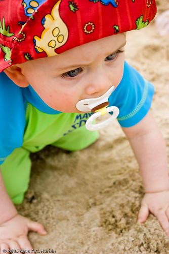 Baby boy on beach in red hat
