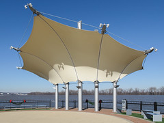 Visit to a metal-frame-supported tensile structure with PVC membrane. (Tim Kiser) Tags: 2016 20160103 christmasdecorations christmasgarland daviesscounty daviesscountykentucky img7753 january january2016 kentucky ohioriver ohioriverriverfront owensboro owensborokentucky pvccoating pvclaminate pvcmembrane smotherspark spencercounty spencercountyindiana benches canopy cantilever cantileverconstruction cantileveredstructure citypark cloudlesssky concertvenue downtown downtownowensboro garland laminatedfabric mastsupports mastsupportedcanopy masts metalpoles outdoorconcertspace outdoorconcertvenue outdoorperformancespace outdoorperformancevenue park parkbenches performanceshelter performancespace performancevenue plaza poles redbows river riverfront riverfrontpark shelter stretchedfabric summerconcertvenue sunny tensile tensilearchitecture tensilecanopy tensilefabric tensilefabriccanopy tensilefabricstructure tensilestructure waterfront waterfrontpark westkentucky westernkentucky unitedstates