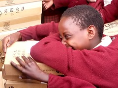 Enkakenya Centre for Excellence pupil Mary spontaneously hugs the new HP computers as they are being unloaded