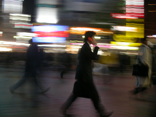 Business man walking and talking on the phone through blurry streetlights.