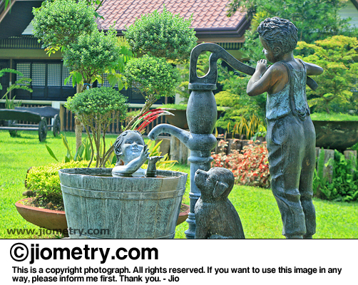 Statue of two kids bathing near the water pump with their pet dog