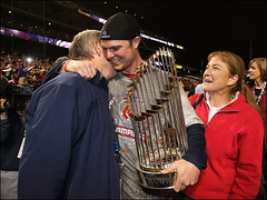 Winning pitcher Jon Lester, with his parents and the World Series trophy.