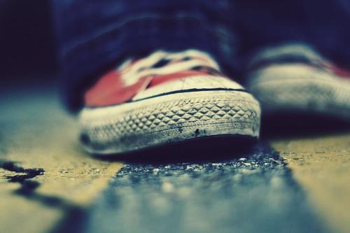 Fotografía de unas zapatillas Converse All Star Chuck Taylor rojas sobre un asfalto rugoso