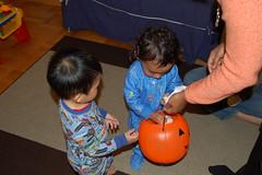 Ronak putting mini pumpkins into the jack-o-lantern