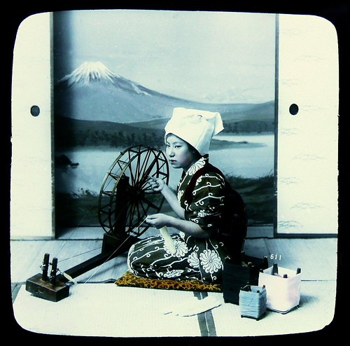 MT. FUJI FROM THE STUDIO -- Geisha in Kimono With a Spinning Wheel Against Painted Backdrop