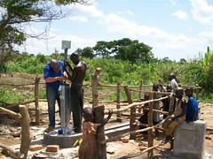 A Nyakarongo resident assists Ned Morgan in installing the pump