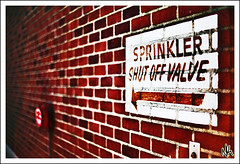 Firewall (i ea sars) Tags: city red urban brick water sign wall fire 50mm paint pattern dof bricks edificio sprinkler valve canon5d arrow architettura architectura canon50mm canonef50mmf14usm architektura  canoneos5d  top20signs budova aplusphoto