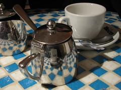 La hora del té, una taza reflejada en la tetera
