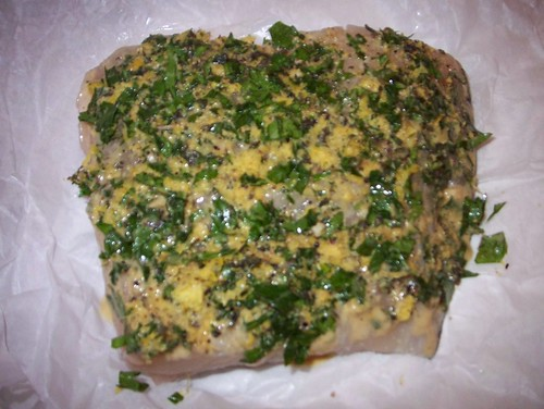 pressing herbs onto halibut