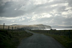 The road to Lenan (greenwood100) Tags: road ireland light sea sky sun sunlight mist nature water tarmac rock skyline clouds fence coast vanishingpoint glare view wind horizon cliffs spray hills coastal lane ethereal winding distance donegal inishowen clonmany urris lenan dunaff coastuk
