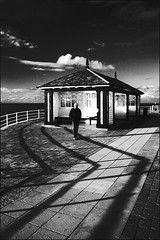 Blurry Happy People (Jim Blob Blann) Tags: shadow sea sky sun white black building beach wales clouds composition digital canon walking fun happy james small grain aberystwyth hut tiles friendly lonely shack midday m