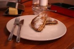 Wentelteefdriehoekjes met poedersuiker op een houten aanrechtblad naast een botervloot en een bakje met daar in een theezeefje met poedersuiker.