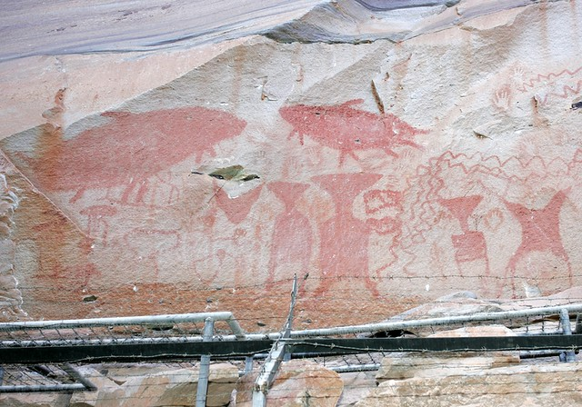 Prehistoric cave paintings of fishermen throwing nets at the catfish (upper left) from Pha Taem National Park. The paintings are possibly 3,000 years old or older.