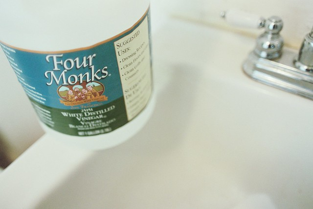 white distilled vinegar ready to create clean, bathroom sink