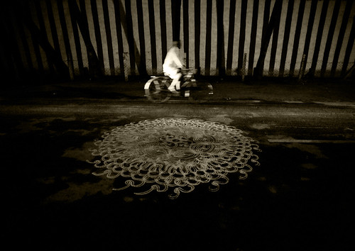 Cyclist Riding Along A Kolam Drawned In The Street Near The Sri Ranganathaswamy Temple, Trichy, India / Eric Lafforgue