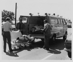 Gross Mortuary's 1970 bright yellow Ford Superior Van Ambulance, loads two accident victims after a wreck in Hot Springs, Arkansas (Dr. Mo) Tags: ford pcs accident injury superior ambulance gross medicine arkansas 1970 van wreck emergency bls ems emt siren hearse combination injured hotsprings funeralhome firstaid injuries emergencylights mortuary procar funeralcoach accidentscene mortician emergencymedicine staroflife ambulancedriver ambulanceservice billdever deathcare drmo redhughes moshinskie jimmoshinskie grossmortuary bunnydever funeralcustoms professionalcarsociety vanambulance beaconray professionalvehicle scenesafety