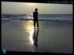 The young man & the sea... (:: niKk clicKs ::) Tags: sunset shadow sea sun india reflection beach silhouette evening nokia sand waves bubbles kerala cochin kochi ernakulam arabiansea nikk fortcochin godsowncountry n73 theyoungmanandthesea queenofarabiansea picnikk binuraj
