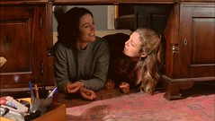 Claire and Tess lie under their father's desk