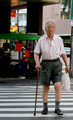 old man in shorts crossing the street with a cane (hey-gem) Tags: street city people urban man guy cane walking walk candid oldman shorts tainancity crossingthestreet pedestrianlane
