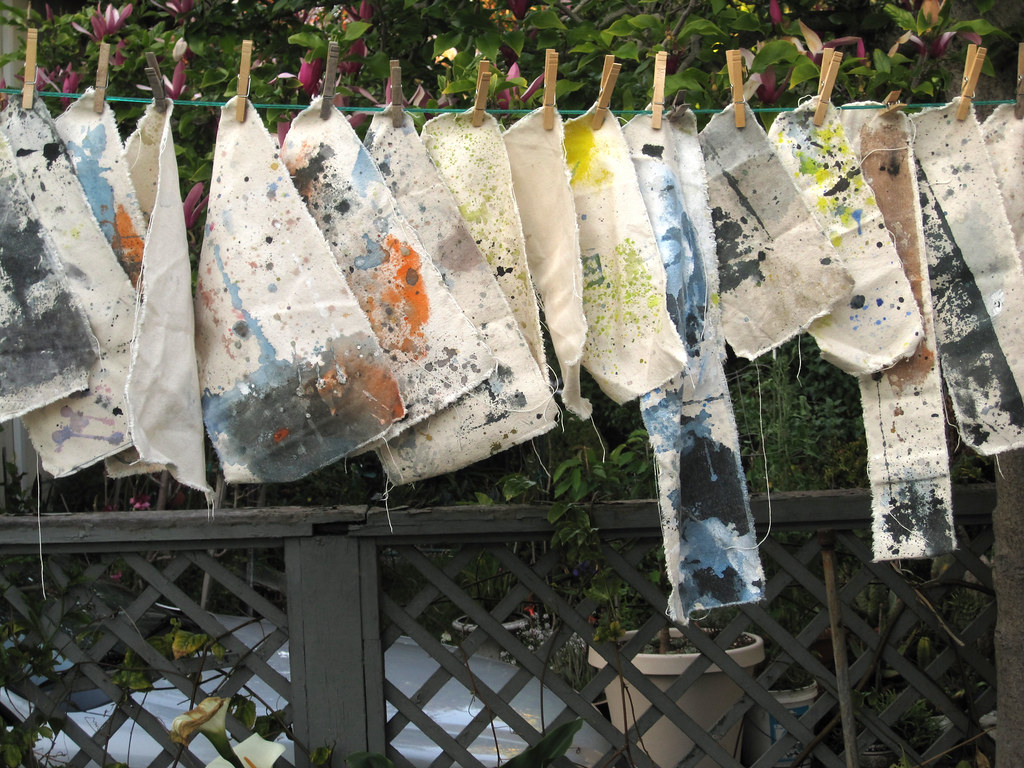 paint on unstretched canvas hanging from a clothes-line