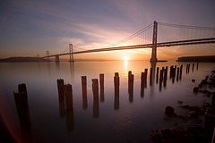 Bay Bridge Sunrise (Tyler Westcott) Tags: sanfrancisco california longexposure sunrise multipleexposure explore baybridge bayarea lowtide hdr ohwell piles refelction nd400 compositeimage nikond40 sanfranciscooakland butihatehdr