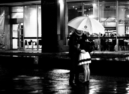 romantic couple kissing in the rain. It is both romantic and