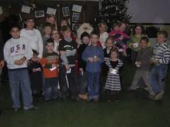 De kerstman tussen de kinderen op het kerstfeest van OCMW Hechtel-Eksel