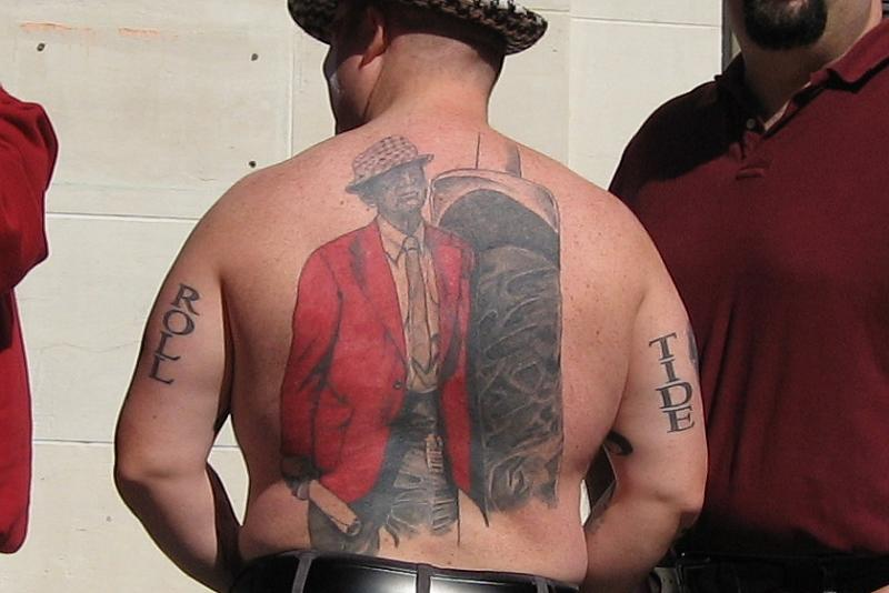 "the ""Roll"" and ""Tide"" tattoos on the back of this man's upper arms."