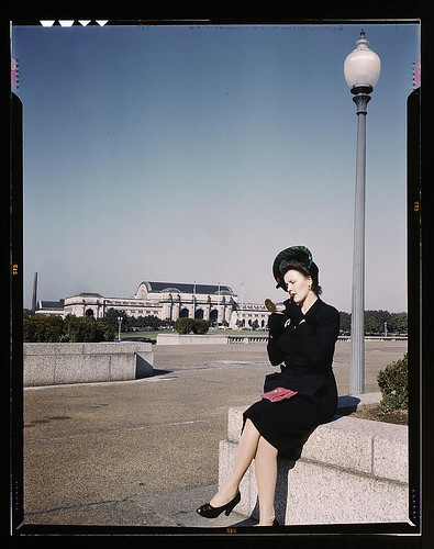Woman putting on her lipstick in a park with Union Station behind her,  Washington,  D.C. (LOC)