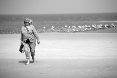 (vauka) Tags: street sea sky bw woman sun cold beach water senior scarf walking sand dof wind empty headscarf clothed streetphotography elder 32 emptyness wangerooge 4102 monochromia