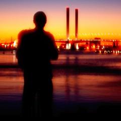 evening fade (mugley) Tags: sunset water silhouette lights evening nikon d70 australia melbourne victoria softfocus docklands squarecrop bloke boltebridge 50mmf14d iso500 shootwideopen minoltazcw100wideconverter vermininc