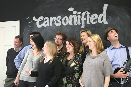 The Carsonified team standing in front of our black board