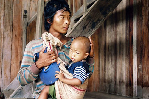 A father waits with his son to receive health care at an MSF clinic in Myanmar