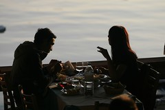 Explaining a point - IMG_6502 (Dimitris Papazimouris) Tags: light sea greek restaurant couple afternoon bodylanguage talk communication greece piraeus mikrolimano canon70200f28 canon30d discussin