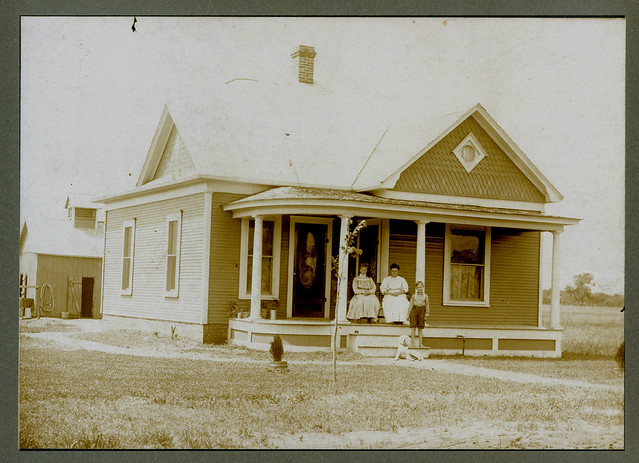 Three people and a dog in front of the house