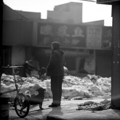 the halted traveller (memetic) Tags: china street old bw woman dog snow 120 6x6 bicycle mediumformat asian blackwhite fuji tl chinese scene flare neopan  nanjing jiangsu acros  p6 pentaconsix sonnar 180mm