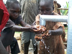 Children wash their hands with the water from the well