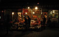 Urumqi Shops (pmorgan) Tags: china street flowers fruit night experiments beijing xinjiang urumqi sellers uigher brassai uygher shopkeppers
