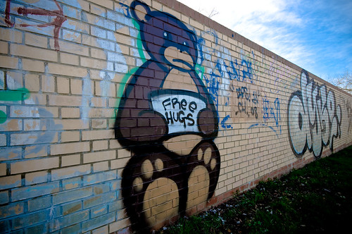 graffiti of big brown bear holding a sign: free hugs