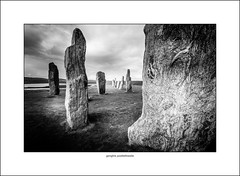 Standing stones at Callanish (Explored) (G. Postlethwaite esq.) Tags: bw callanish hebrides isleoflewis scotland sigma1020 blackandwhite monochrome photoborder wideangle loch water