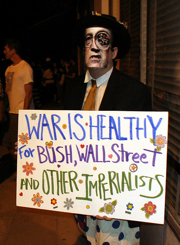 "A man wearing a cyborg Dick Cheney mask holds a sign reading, ""War is healthy for Bush, Wall Street, and other imperialists."""
