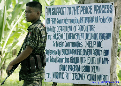 A young Moro rebel standing infront of the sign board at MILF out post, ( A special program from USAID-GEM) inside the MILF Camp Darapanan in Sultan Kudarat, Southern Philippines by mark navales.