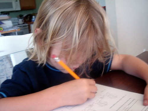 k doing schoolwork, hair in his face
