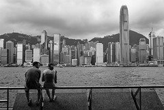 Hong Kong (TGKW) Tags: city portrait sky people blackandwhite woman man mountains water skyline architecture clouds island couple sitting skyscrapers candid rail hills hong kong promenade sha tsim tsui 4498